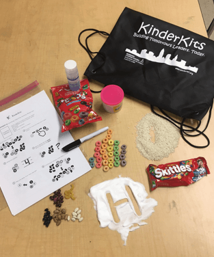 KinderKit resource bag filled with skittles, shaving cream, beans, rice, and more.