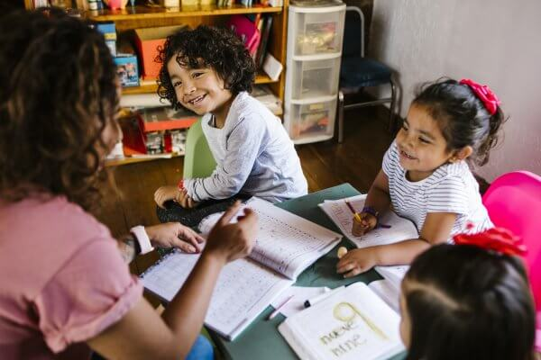 mexican children and mother at home homeschooling spanish learning numbers
